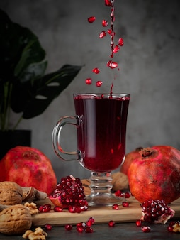 Fresh pomegranate juice in a glass with pomegranates and walnuts lie around