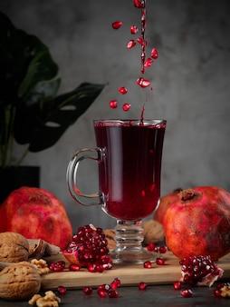 Свежий гранатовый сок в стакане с гранатами и грецкими орехами лежат вокруг