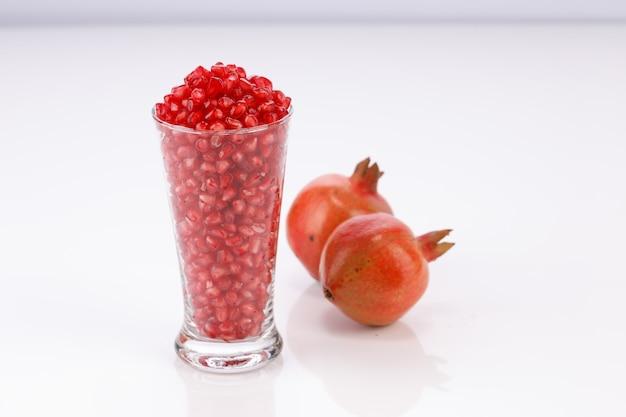 옆에 신선한 과일이 있는 유리 용기에 배열된 신선한 석류 씨앗