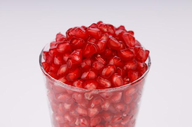 흰색 배경이 분리된 유리 용기에 배열된 신선한 석류 씨앗