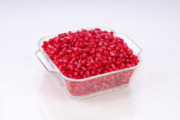 흰색 배경에 정사각형 유리 용기에 배열된 신선한 석류 씨앗.