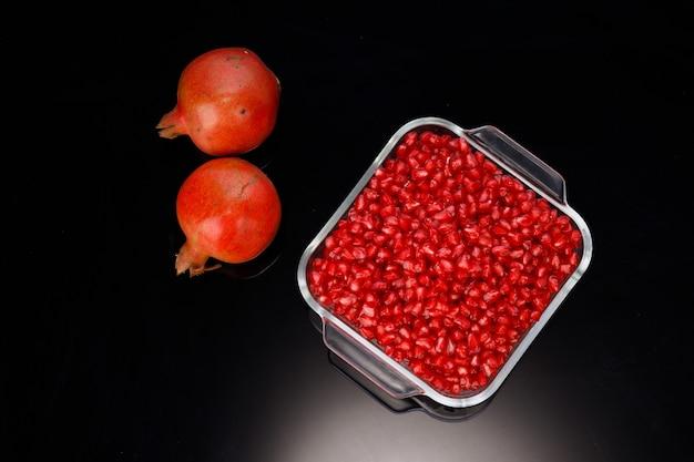 신선한 과일이 옆에 놓여 있는 정사각형 유리 용기에 배열된 신선한 석류 씨앗