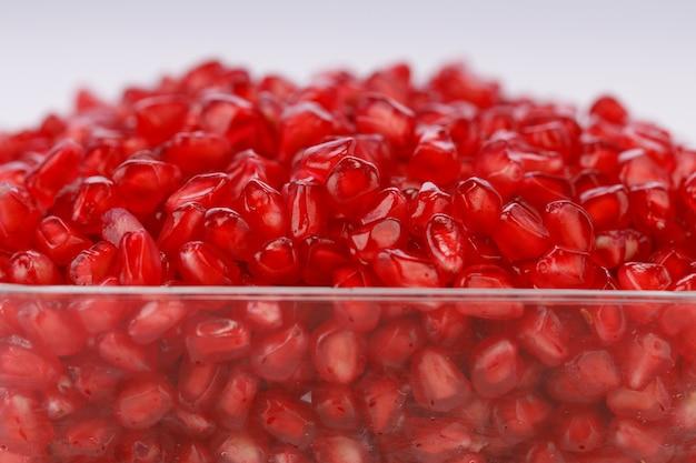 흰색 배경이 분리된 정사각형 유리 용기에 배열된 신선한 석류 씨앗