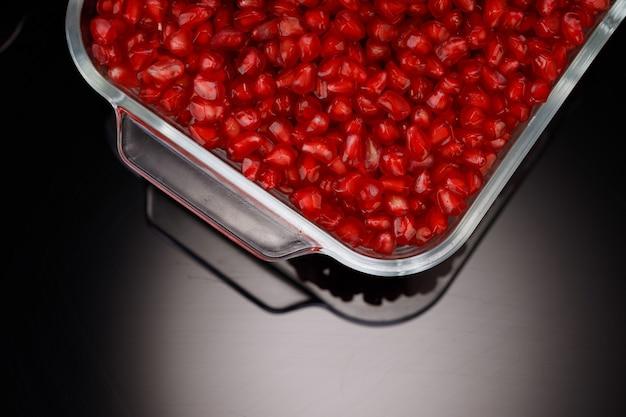 정사각형 유리 용기에 배열된 신선한 석류 씨앗