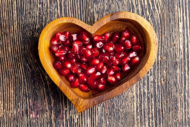 Свежие семена граната в миске в форме сердца