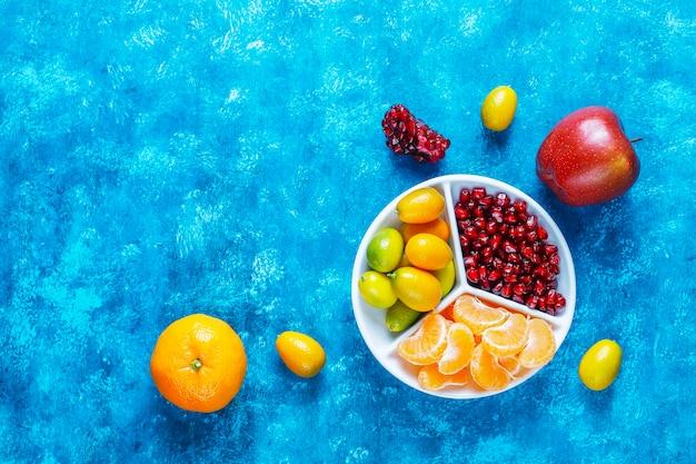 신선한 석류 씨앗, 만다린 조각 및 금귤 과일.