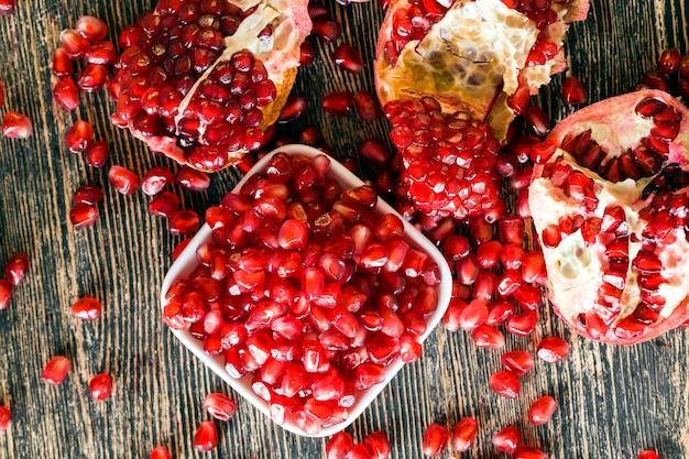 キッチンテーブルの新鮮なザクロの種、ザクロジュースを使用したデザートと肉の調理、ザクロの種のクローズアップ