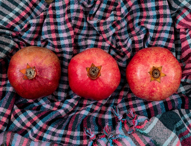 Fresh pomegranate on striped cloth top view