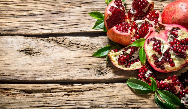 Fresh pomegranate with leaves . on a wooden background. free space for text .