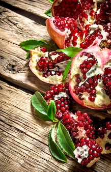 Fresh pomegranate with leaves . on a wooden background.