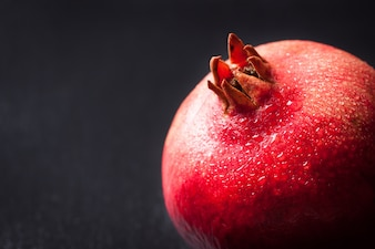 Fresh pomegranate with water droplets on a dark background