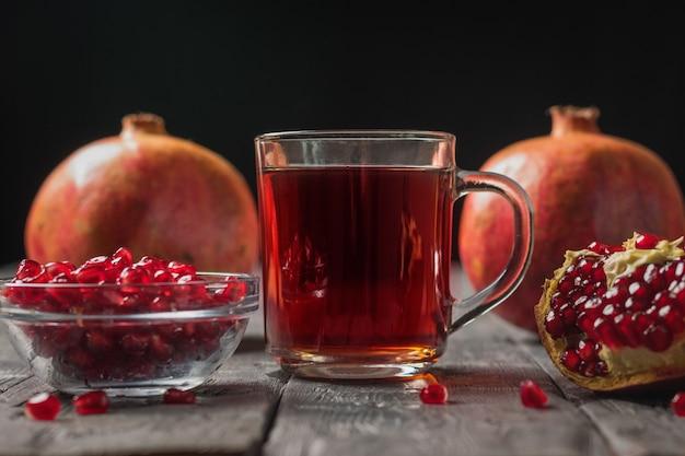Свежие гранаты и стеклянная кружка гранатового сока. напиток полезен для здоровья.