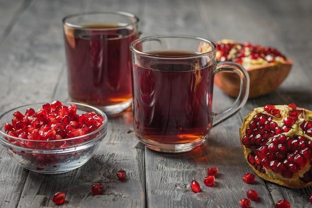 Свежие гранаты и две стеклянные кружки гранатового сока. напиток полезен для здоровья.