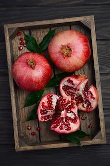 Fresh pomegranates on dark wooden background.
