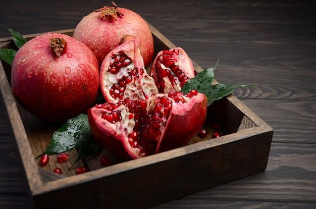 Fresh pomegranates on dark wooden table.