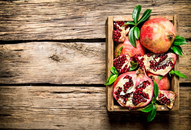 Fresh pomegranates in an old box with leaves. on wooden background. free space for text . top view