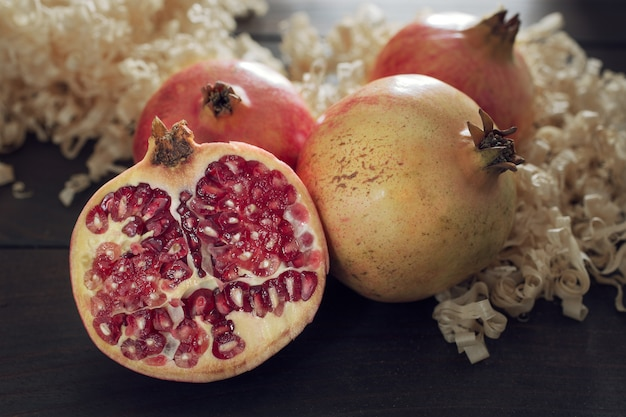 Fresh pomegranates and sliced pomegranate with seeds on wooden table