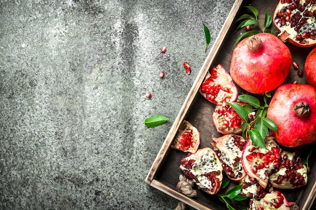 Fresh pomegranates on a wooden tray on a rustic background