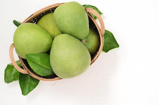 新鮮なザボン、ザボン、グレープフルーツ、竹かごの白いセメントの背景にシャドック。秋の季節のフルーツ、トップビュー、フラットレイ、卓上ショット。