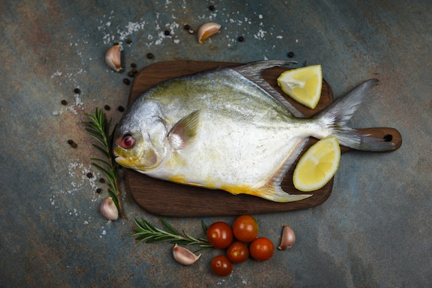 Fresh pomfret fish with herbs spices rosemary tomato and lemon on wooden cutting board and black plate background - raw black pomfret fish