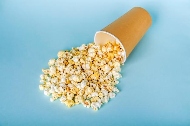 Свежий попкорн разбросаны из бумажной коробки на синем столе. концепция закуски кино. еда для просмотра фильмов и развлечений.
