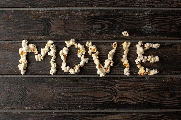 Свежий попкорн вкусно соленое кино слово сформировалось на коричневом деревенском деревянном столе