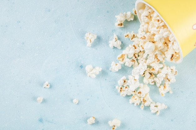 Fresh popcorns spread over the blue table out of the box