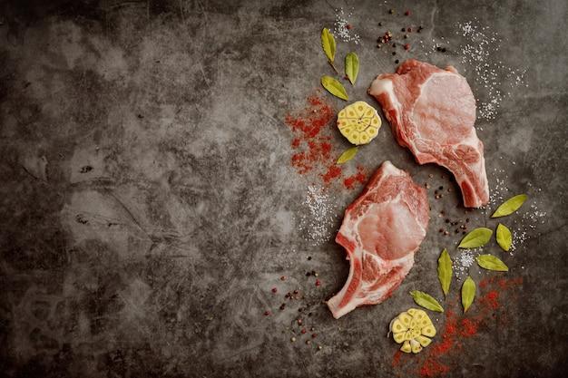 Ребро и специи свежие свиные отбивные на сером фоне с копией пространства. вид сверху.