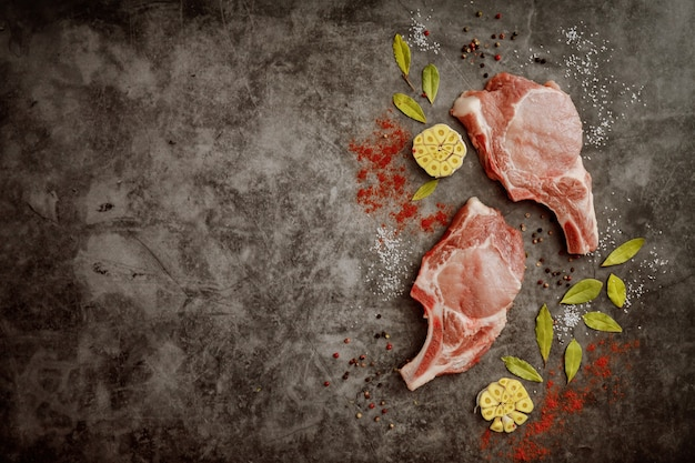 Fresh pork chops rib and spices on gray background with copy space. top view.