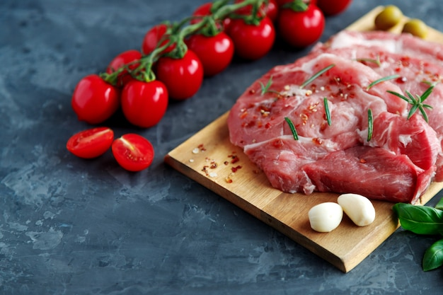 Fresh pork chops in spices on a wooden board, near cherry tomatoes on a branch and garlic cloves on a dark background.