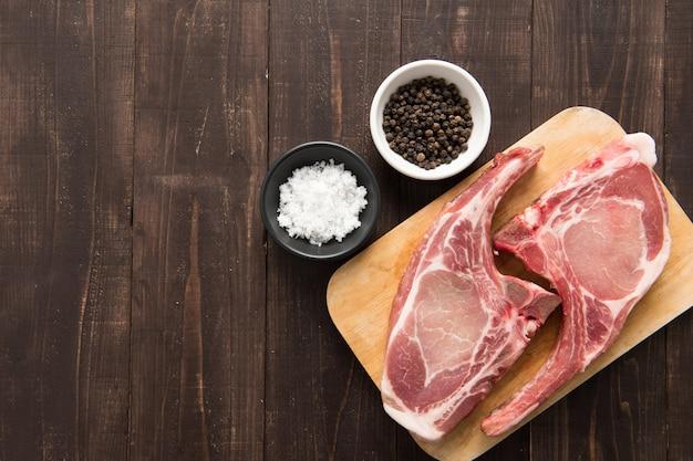 Свежие свиные отбивные с перцем и солью на деревянном фоне