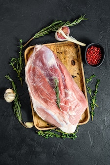 Fresh pork cuts. raw meat with spices.  hind leg steak. black background. top view
