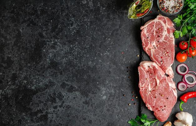 Стейки из свежего свиного филе с овощами и специями на темном фоне