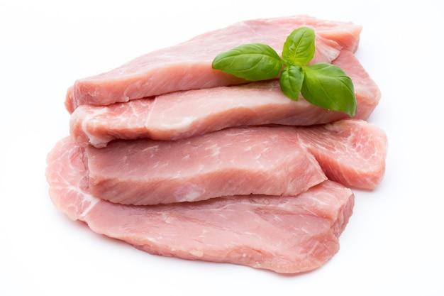 Свежее филе свинины с базиликом на белом