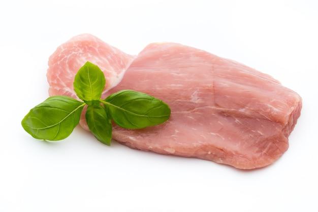 Свежее филе свинины с базиликом на белом.