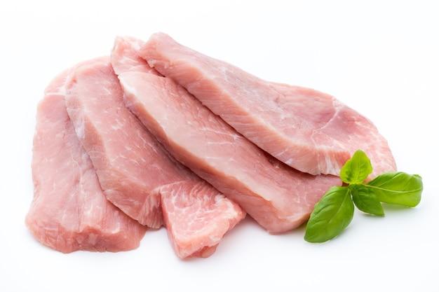 白地にバジルを添えた新鮮な豚ヒレ肉