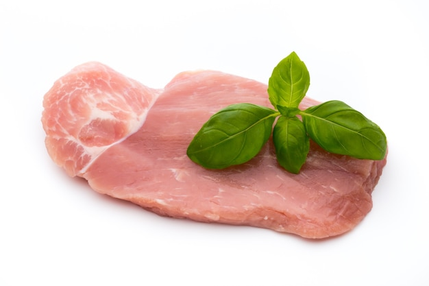Fresh pork fillet with basil on a white background