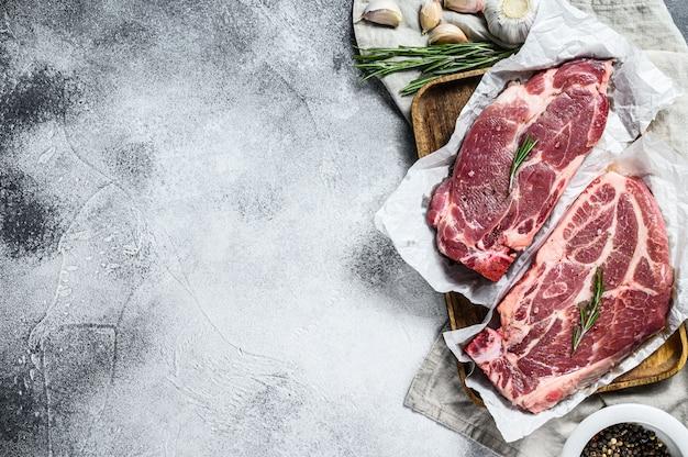 신선한 돼지 고기 스테이크. 양피지에 대리석 고기. 회색 벽. 평면도. 텍스트를위한 공간