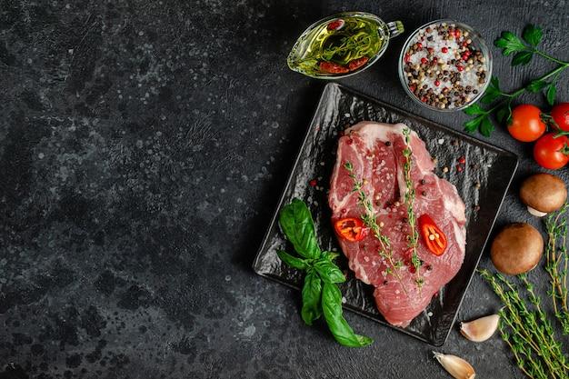 Свежий стейк из свинины на грифельной тарелке с овощами, специями и зеленью на темном фоне
