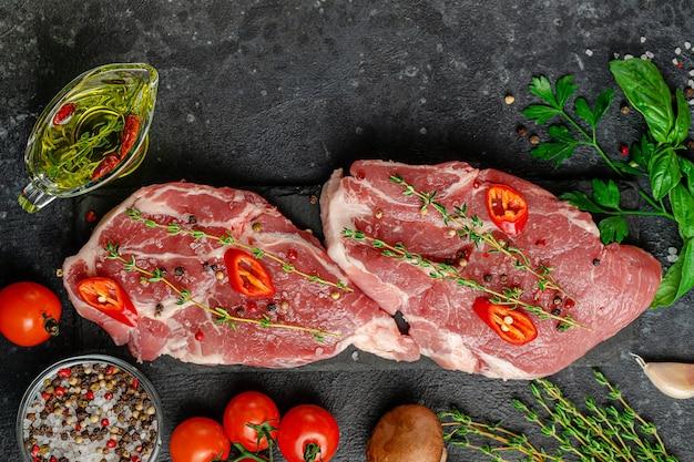Свежие стейки из свинины с зеленью, овощами и специями на фоне черного сланца