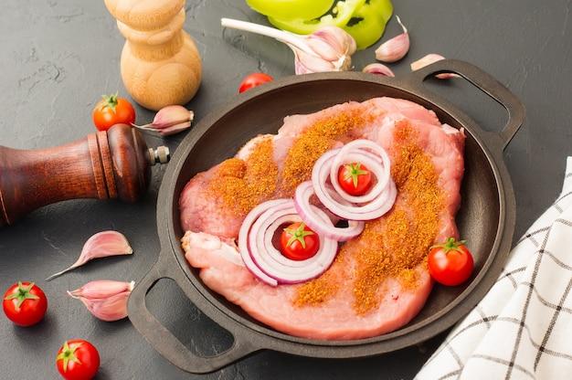 フライパンにスパイス、玉ねぎ、トマトを入れた新鮮な豚ヒレ肉。料理と健康的な食事の概念。