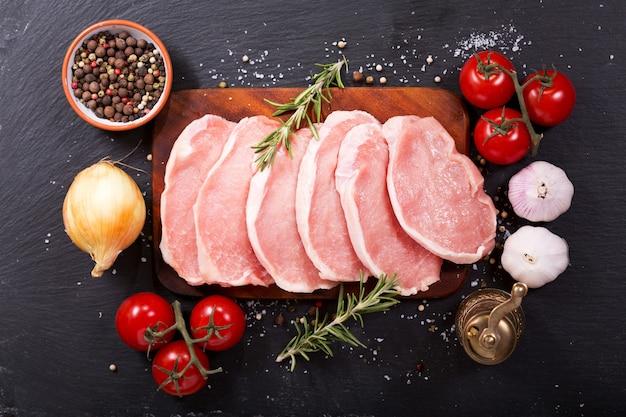 暗い背景で調理するための材料と新鮮な豚肉