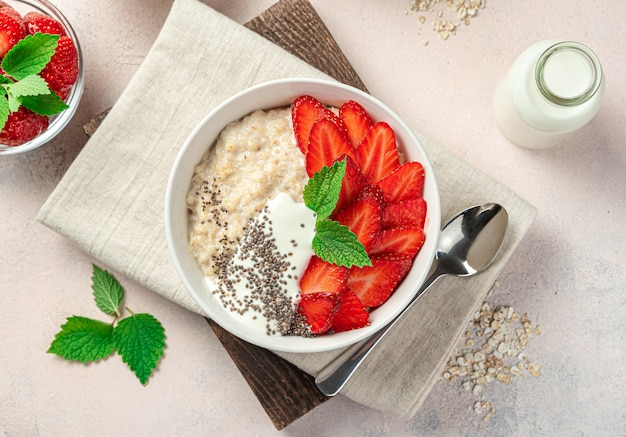 Fresh porridge with berries and chia seeds on a light pink background
