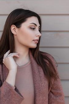 야외 빈티지 나무 벽 근처 유행 코트에 섹시 한 입술으로 아름 다운 갈색 머리를 가진 신선한 초상화 매력적인 여성 젊은 여자. 귀여운 세련된 여자 패션 모델. 아름다움 세련된 아가씨.