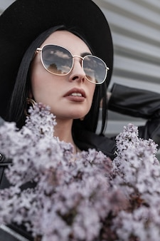 Fresh portrait charming brunette woman in luxurious fashionable hat in sunglasses in black jacket with beautiful lilac flowers near metal vintage wall in city. sexy girl model and beautiful plants.