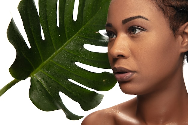 新鮮。モンステラの葉と白いスタジオの背景に分離された美しいアフリカ系アメリカ人女性の肖像画。美容、ファッション、スキンケア、化粧品のコンセプト。広告のコピースペース。手入れの行き届いた肌、みずみずしい表情。