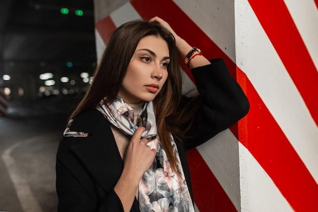 道路の近くの通りのモダンな赤白の柱の近くにファッショナブルなシルクのショールでスタイリッシュな黒のコートを着た新鮮な肖像画のかなり若い女性。街の流行の服を着た美しいエレガントな女性モデル。