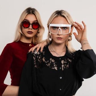 Свежий портрет двух подружек блондинок в модных цветных молодежных очках в красных и черных платьях возле серой винтажной стены