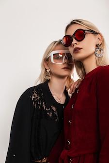 세련된 멋진 안경에 세련된 빨강-검정 옷을 입은 신선한 초상화 젊은 아름다운 레즈비언이 나란히 서 있습니다. 프리미엄 사진