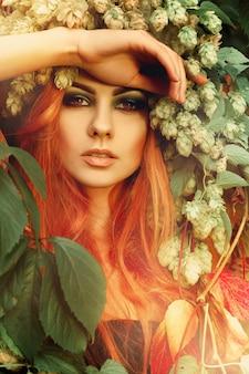 屋外の頭にホップの花輪と葉のセクシーな赤毛の女性の新鮮なportriat